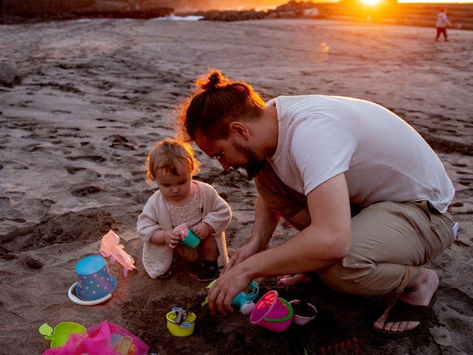 Padre e hija jugando en la playa