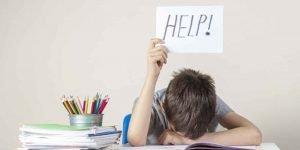 Niño tumbado sobre un libro sujetando un cartel pidiendo ayuda
