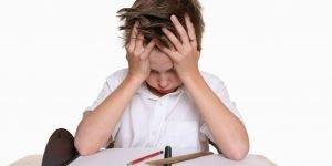 Niño con la cabeza apoyada en las manos frente a un cuaderno en blanco