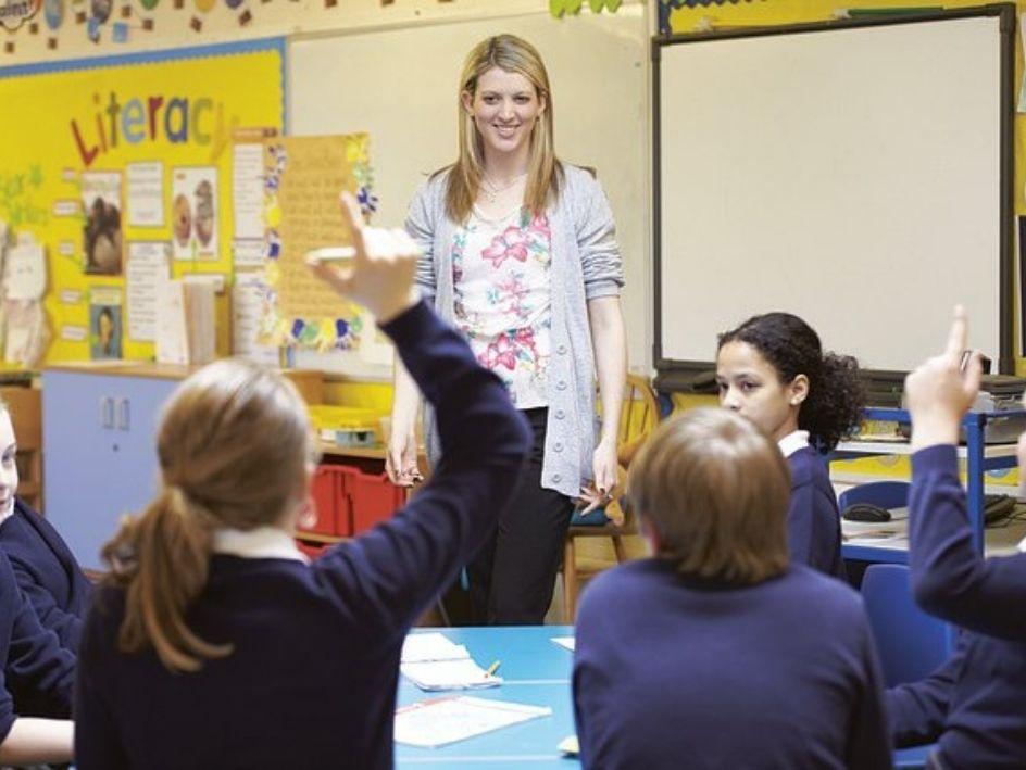 Niños en clase levantando la mano para responder a la profesora