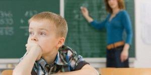 Niño con dificultades de aprendizaje distraído ante las lecciones de la profesora
