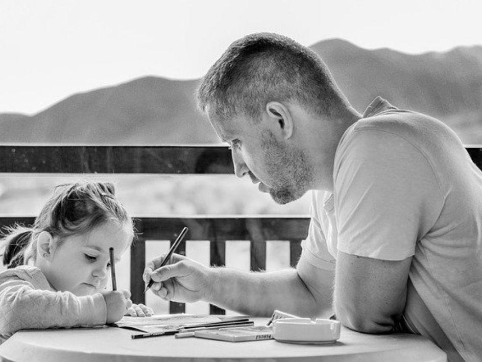Un padre ayuda a su hija pequeña a hacer los deberes