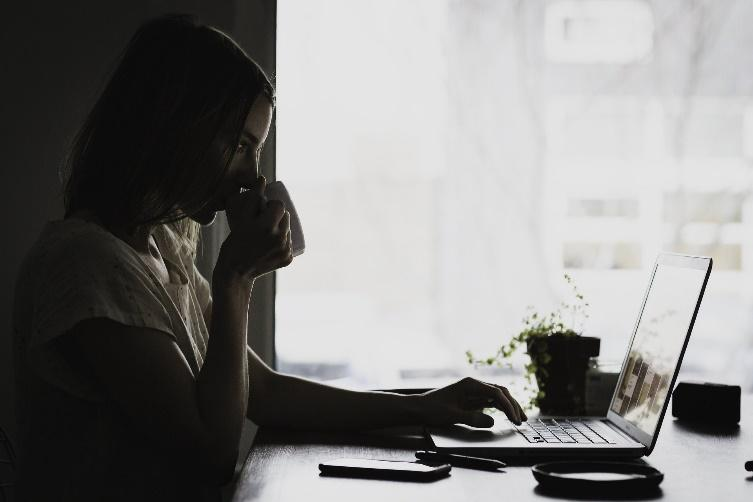 Mujer tomando un café delante del ordenador